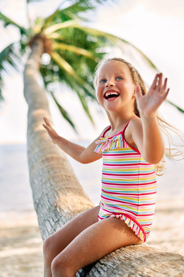 Happy little blonde girl playing on the beach sitting on palm tree. stock photos