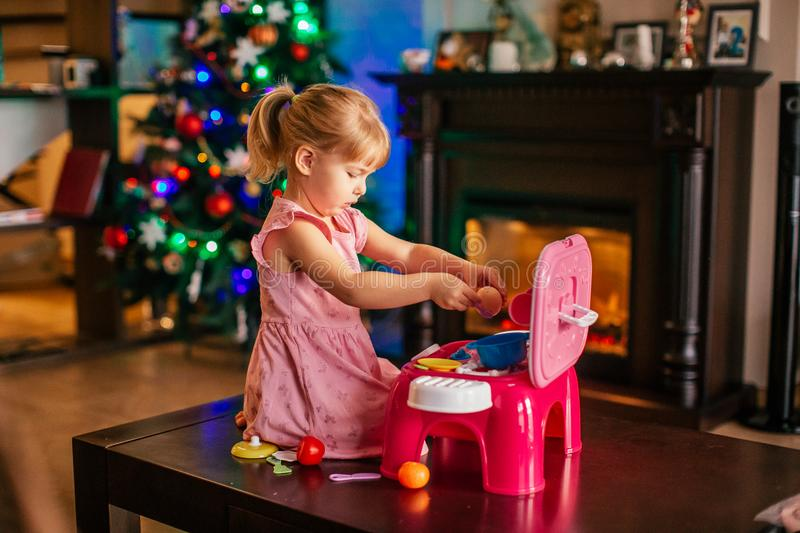 Happy little blonde girl playing near Christmas tree with toy kitchen. Xmas morning in decorated living room with fireplace and stock image