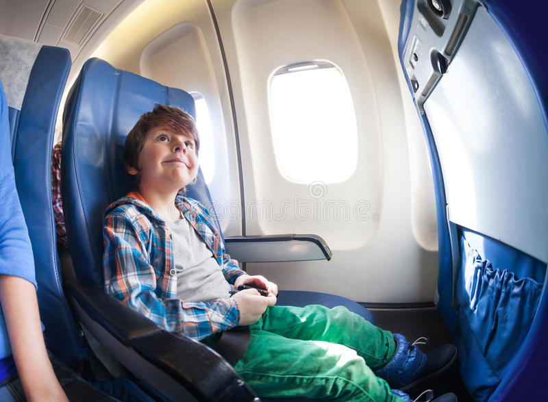 Happy little boy in airplane seat sit by window. Happy little boy sit by the window in commercial jet pane going to vacation royalty free stock photography