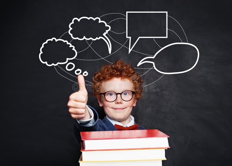 Happy little boy and blank speech clouds bubbles. Smart kid in glasses on school blackboard background stock images