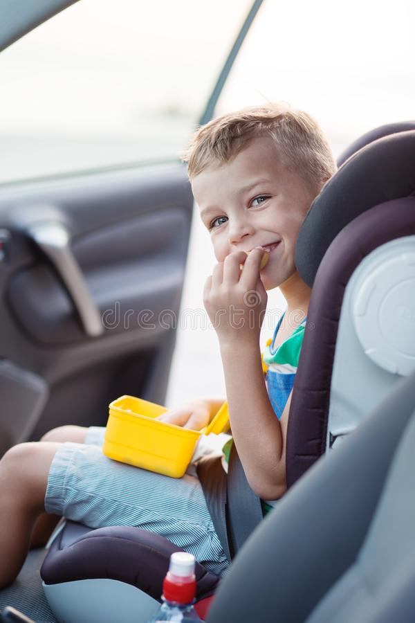 Happy little boy in the car eating royalty free stock images