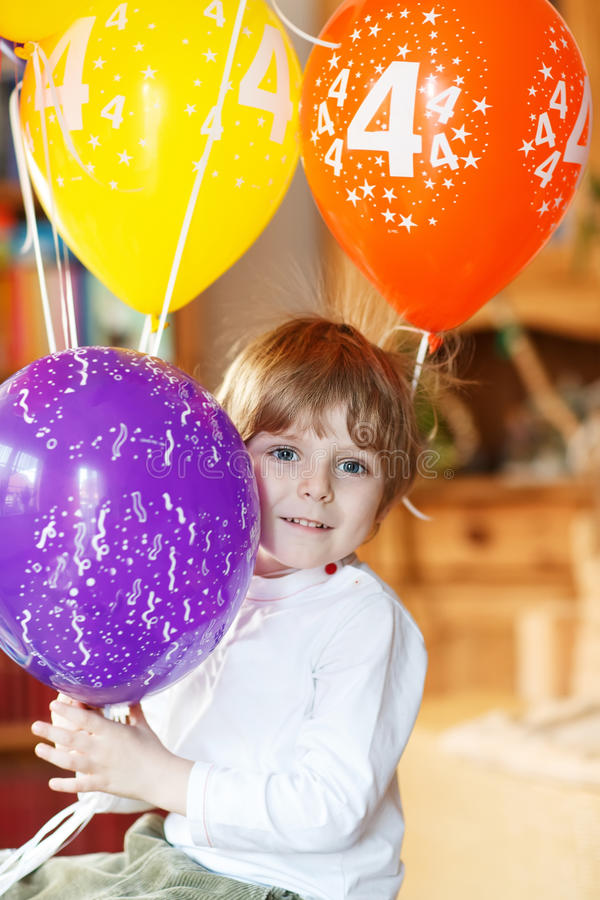 Happy little boy celebrating his 4 birthday with colorful balloons. Indoor in kidsroom stock photography