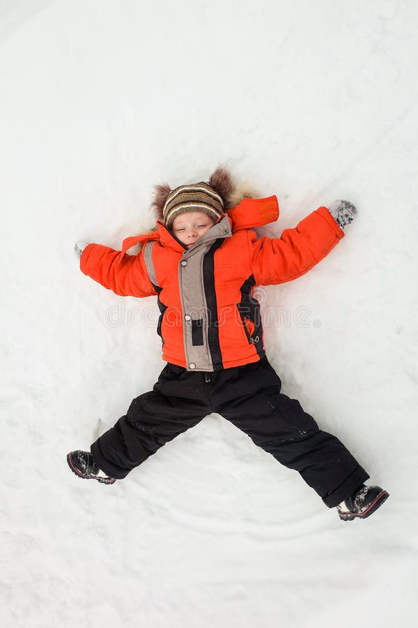 Happy little boy child laying on snow. Naughty mischievous kid. Winter activity royalty free stock image