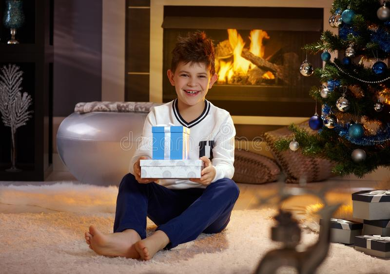 Happy little boy with christmas presents. Happy boy smiling, holding christmas present, sitting on floor by christmas tree royalty free stock images