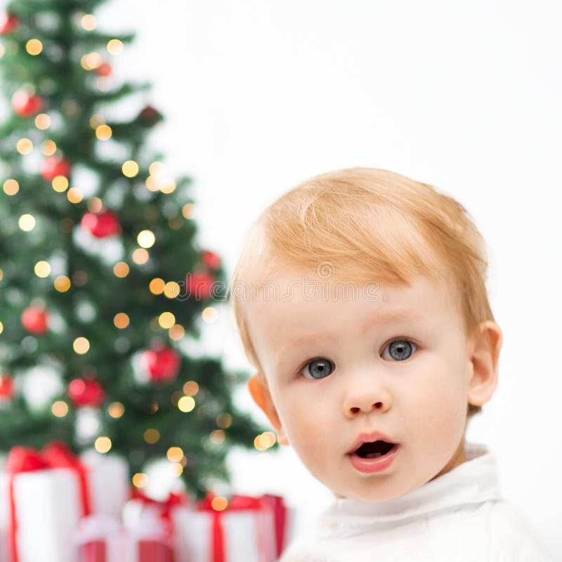 Happy little boy with christmas tree and gifts. Winter, people, x-mas, happiness concept - happy little boy with christmas tree and gifts royalty free stock image