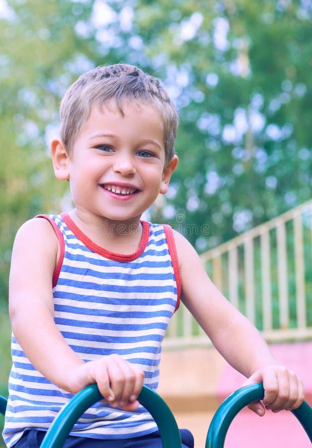 Happy little boy climbing on children playground on beautiful summer day. stock photos