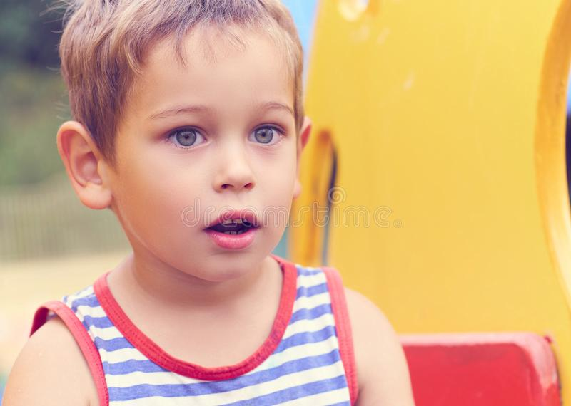 Happy little boy climbing on children playground on beautiful summer day. stock photography