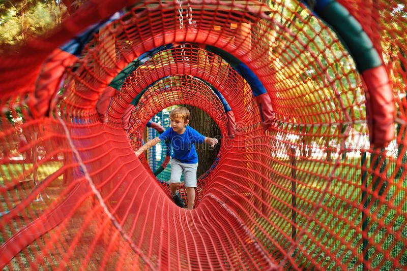 Happy little boy climbing rope obstacle activity on outdoors playground. Happy and healthy childhood. Modern adventure park for stock photography