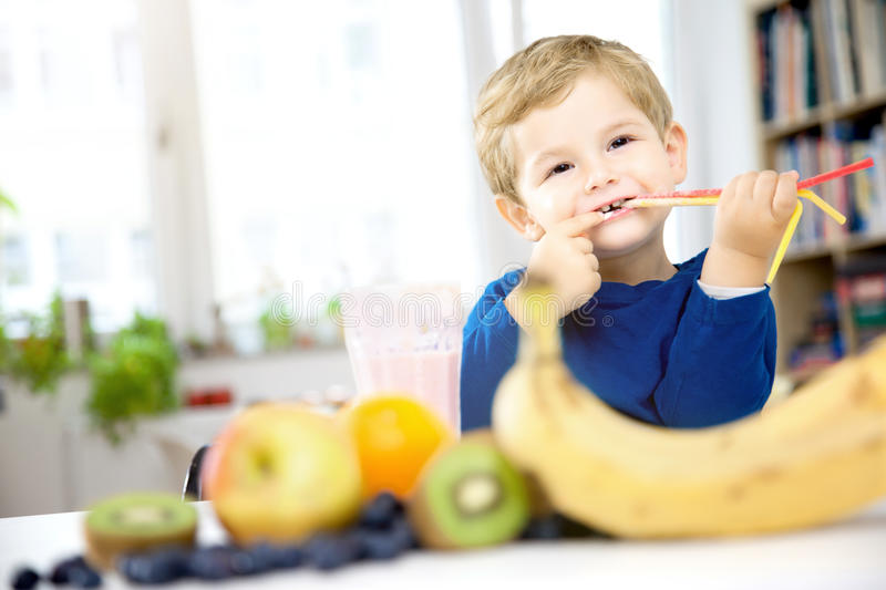 Happy Little Boy drinking a Healthy Smoothie in his Cozy home, w royalty free stock photography