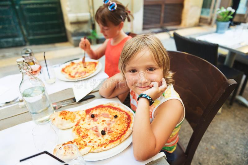 Happy little boy eating kid`s pizza in the restaurant. stock photo