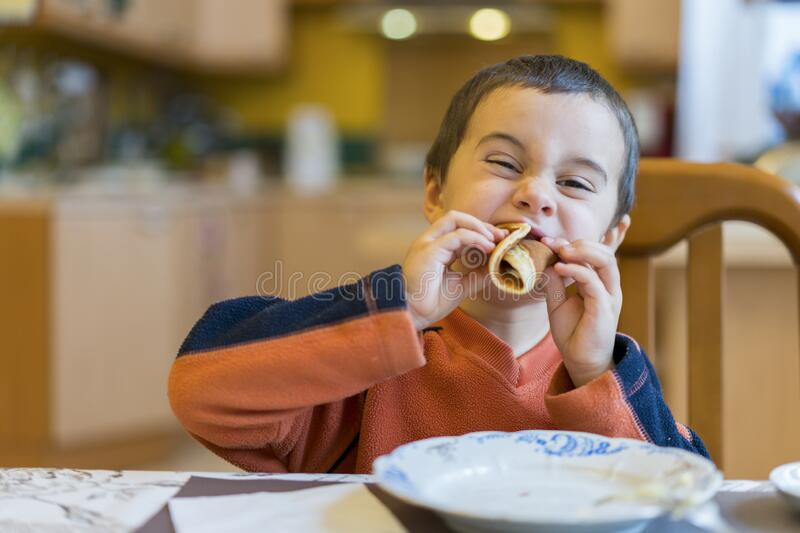 Happy little boy eats pancakes hands. Portrait of small cute little boy child caucasian sitting by the table at home stock photo