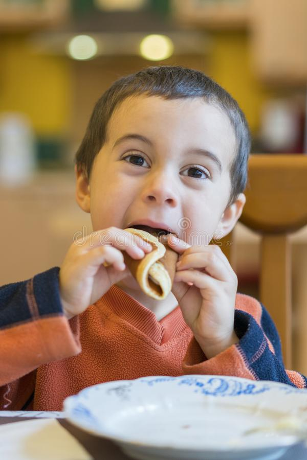 Happy little boy eats pancakes hands. Portrait of small cute little boy child caucasian sitting by the table at home eating royalty free stock photos