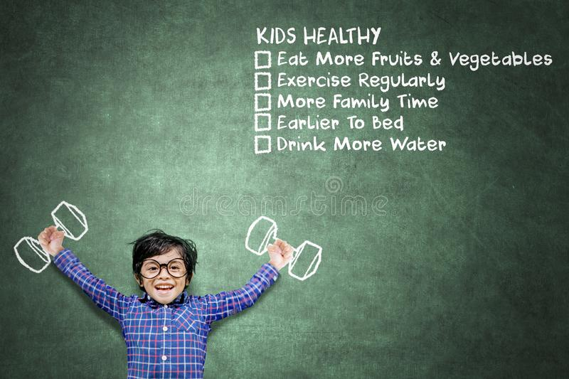 Happy little boy exercising near lists of kids healthy. Happy little boy exercising with dumbbells while standing with lists of kids, healthy in chalkboard royalty free stock photo