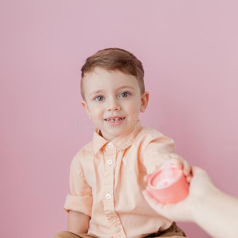 Happy little boy with a gift . Photo isolated on pink background. Smiling boy holds present box. Concept of holidays and birthday.  stock image