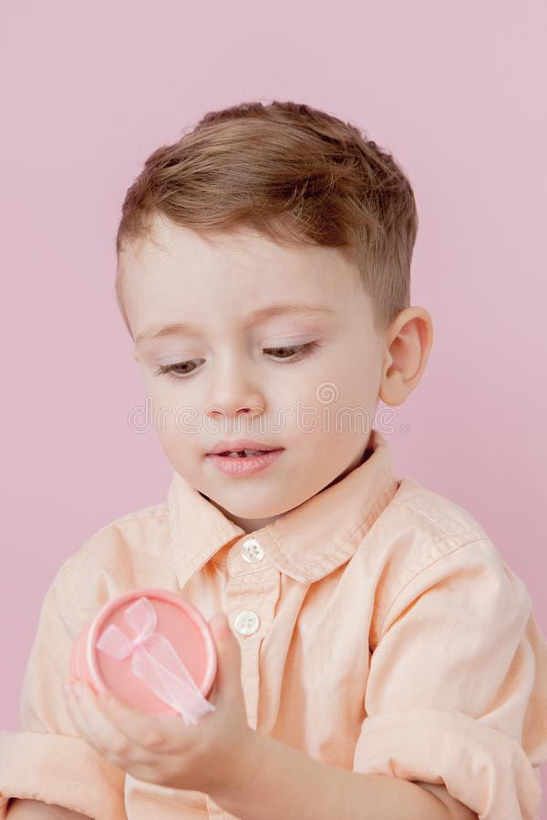 Happy little boy with a gift . Photo isolated on pink background. Smiling boy holds present box. Concept of holidays and birthday.  royalty free stock photography