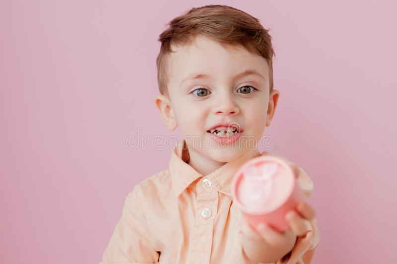Happy little boy with a gift . Photo isolated on pink background. Smiling boy holds present box. Concept of holidays and birthday.  royalty free stock photo