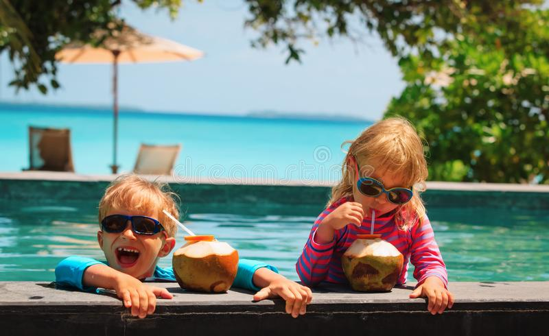 Happy little boy and girl drinking coconut cocktail on beach resort royalty free stock photos