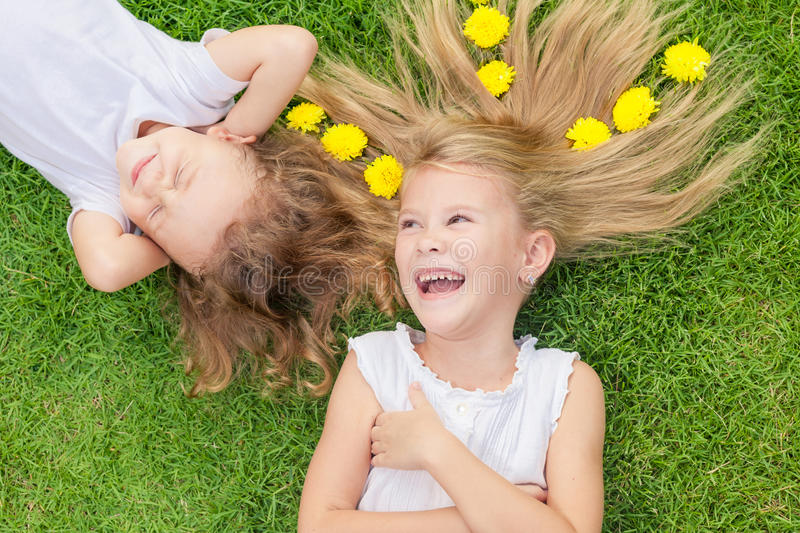 Happy little boy and girl lying on the grass royalty free stock photography