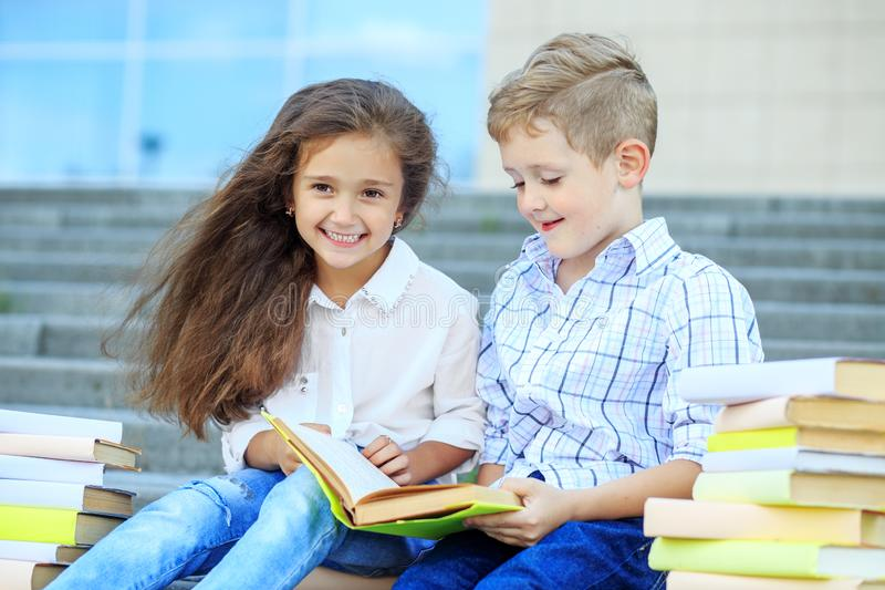 Happy little boy and girl are reading a book. The concept is back to school, education, reading, friendship and family stock photos