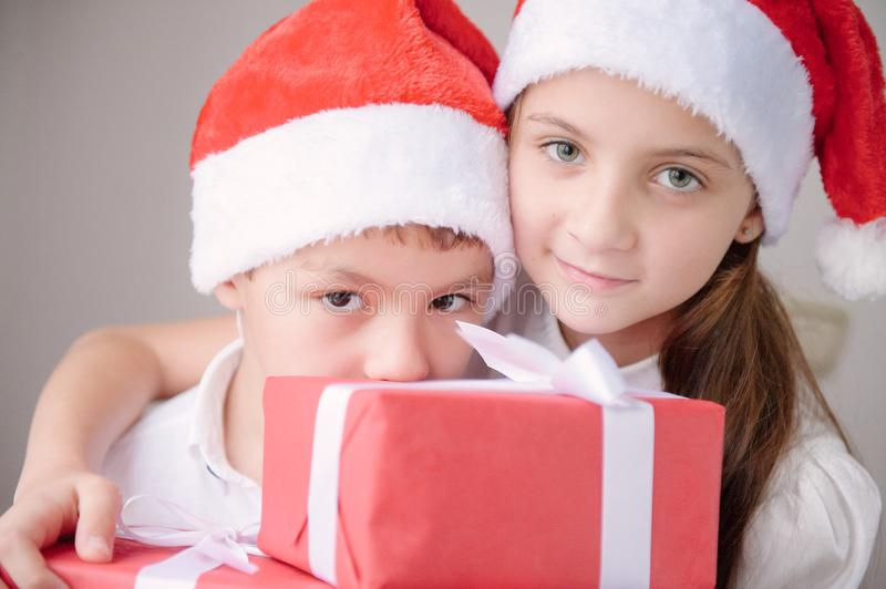 Boy and girl in santa hat holding box with gift royalty free stock images