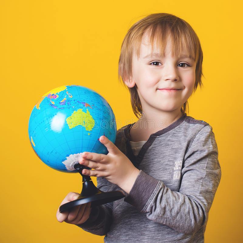 Happy little boy with globe, isolated on yellow. Funny kid studying educational globe model. School and education concept. Curious royalty free stock photo
