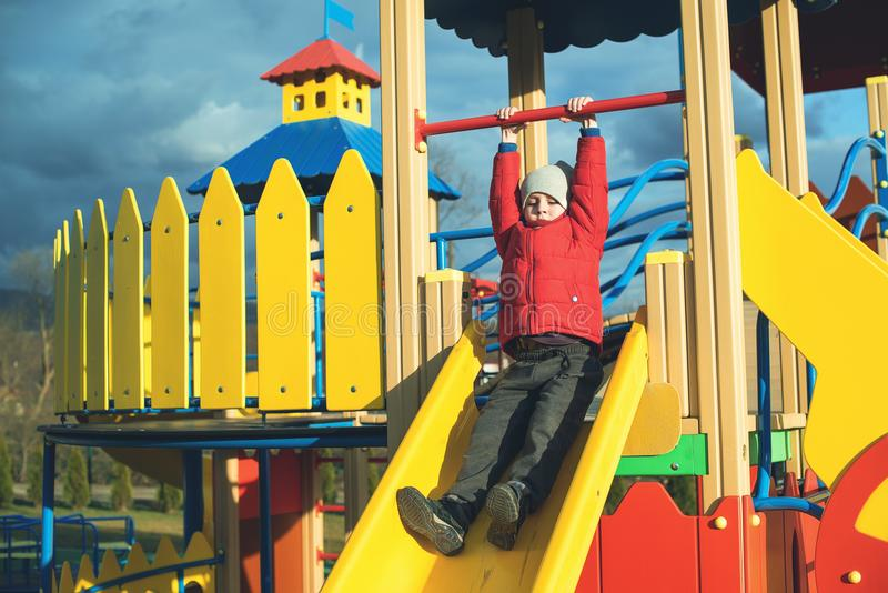 Happy little boy have fun and sliding on colorful modern playground in park. stock photography