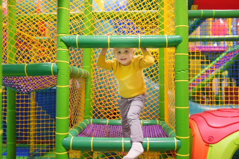 Happy little boy having fun in amusement in play center. Child playing on indoor playground. Active birthday party for preschooler kids royalty free stock photo
