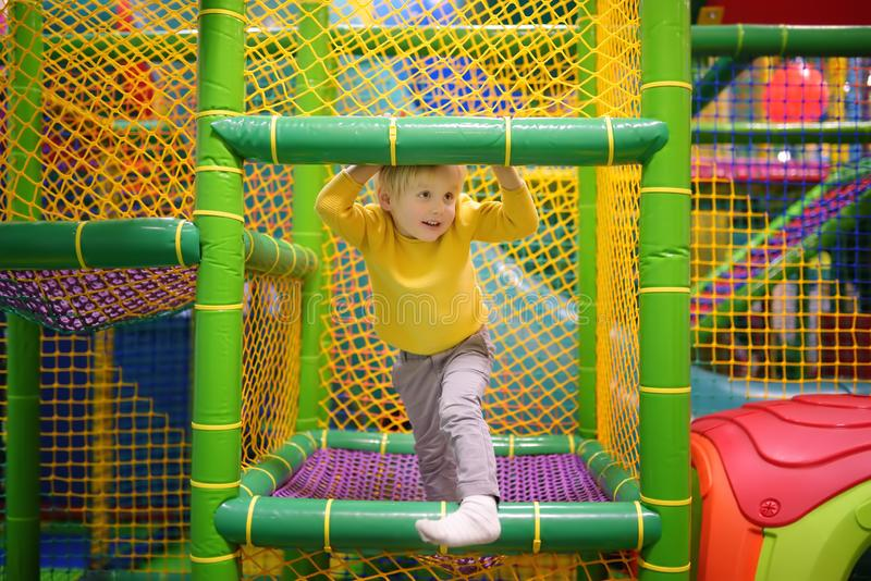 Happy little boy having fun in amusement in play center. Child playing on indoor playground. Active birthday party for preschooler kids royalty free stock photos