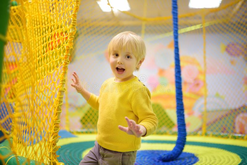 Happy little boy having fun in amusement in play center. Child playing on indoor playground. Active birthday party for preschooler kids stock photo