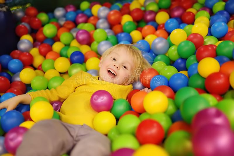 Happy little boy having fun in ball pit with colorful balls. Child playing on indoor playground. Kid jumping in ball pool royalty free stock photos