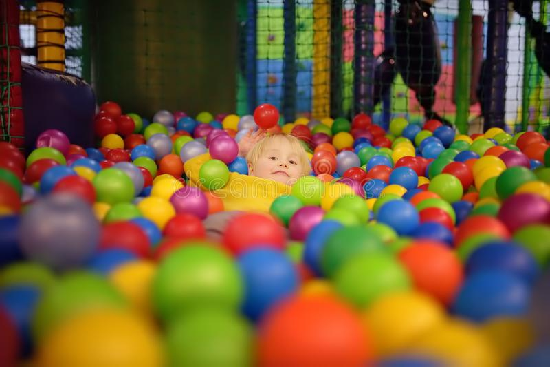 Happy little boy having fun in ball pit with colorful balls. Child playing on indoor playground. Kid jumping in ball pool stock photo