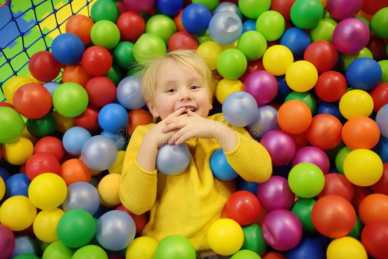 Happy little boy having fun in ball pit with colorful balls. Child playing on indoor playground. Kid jumping in ball pool stock photography