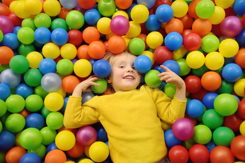 Happy little boy having fun in ball pit with colorful balls. Child playing on indoor playground. Kid jumping in ball pool stock image