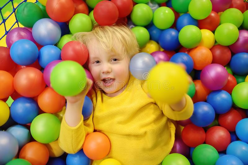 Happy little boy having fun in ball pit with colorful balls. Child playing on indoor playground. Kid jumping in ball pool royalty free stock photography