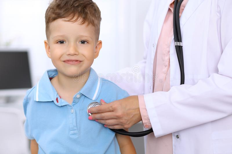 Happy little boy having fun while is being examine by doctor by stethoscope. Health care, insurance and help concept.  royalty free stock photography