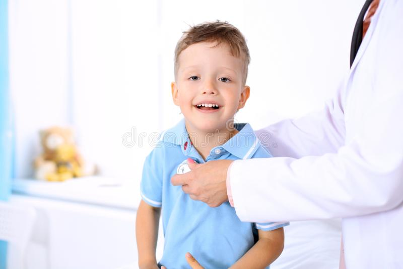 Happy little boy having fun while is being examine by doctor by stethoscope. Health care, insurance and help concept.  stock images