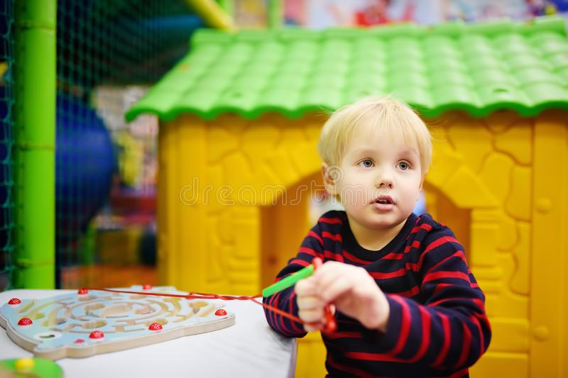 Happy little boy having fun with educational toy in play center stock image