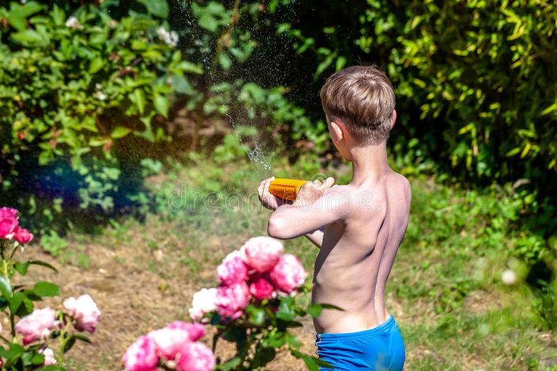 Happy little boy having fun with squirt gun in the garden.  royalty free stock photos