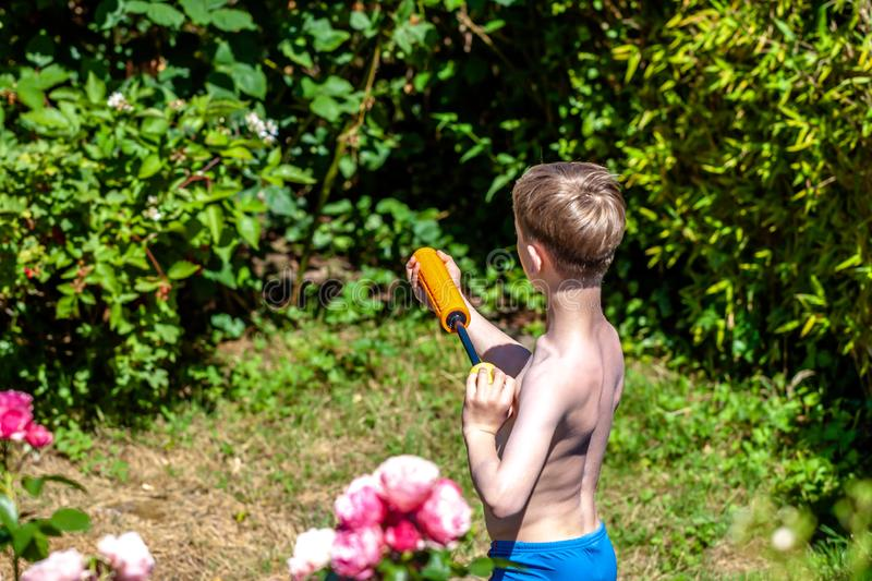 Happy little boy having fun with squirt gun in the garden.  royalty free stock photo