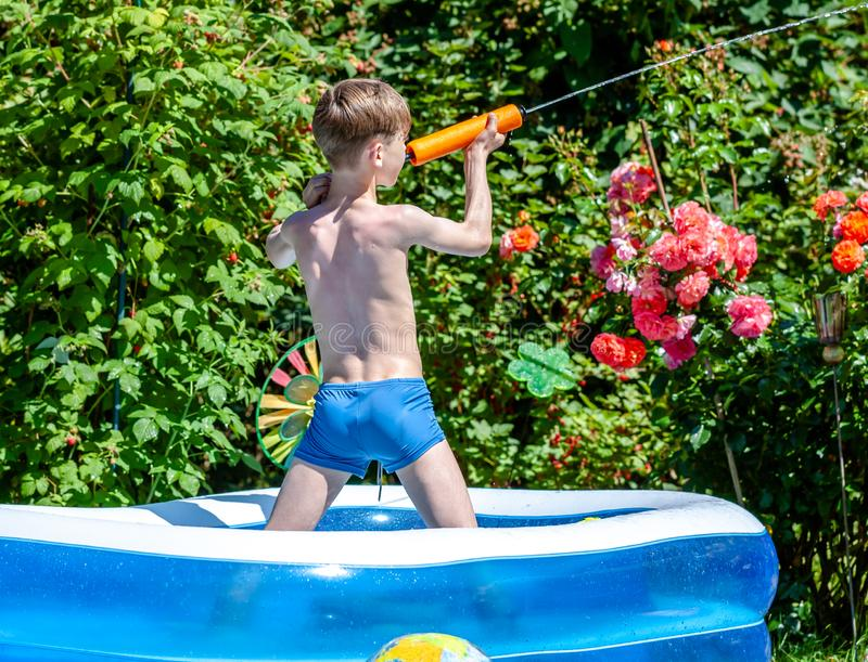 Happy little boy having fun with squirt gun in pool.  royalty free stock photography