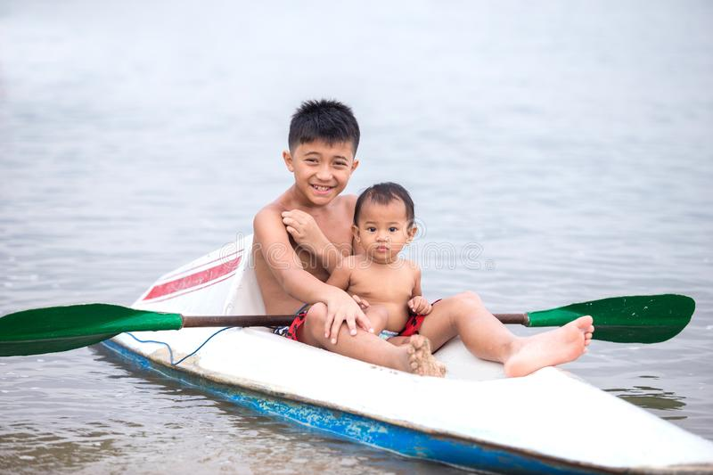 Happy little boy with his sister paddling kayak on the river in royalty free stock images