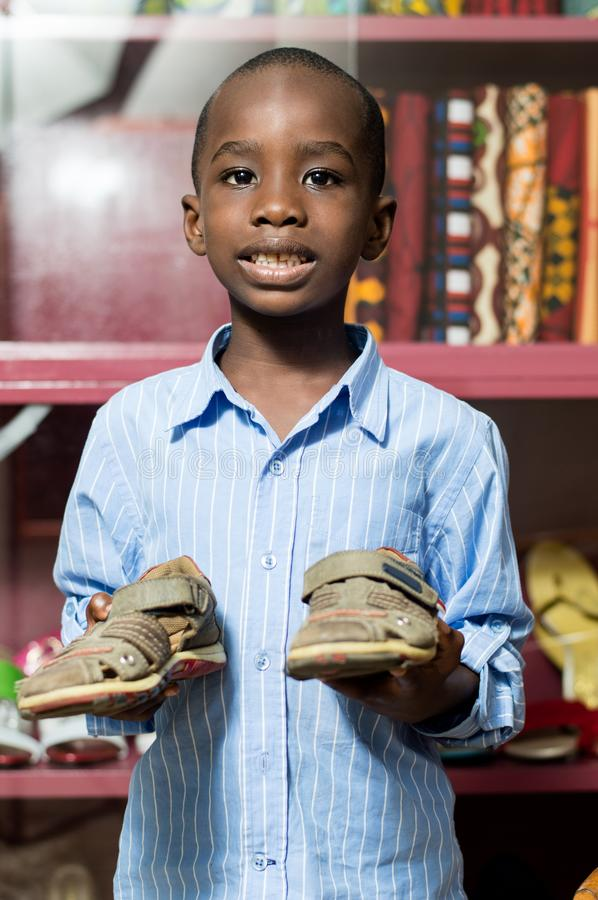Happy little boy holding shoes in a store stock photography