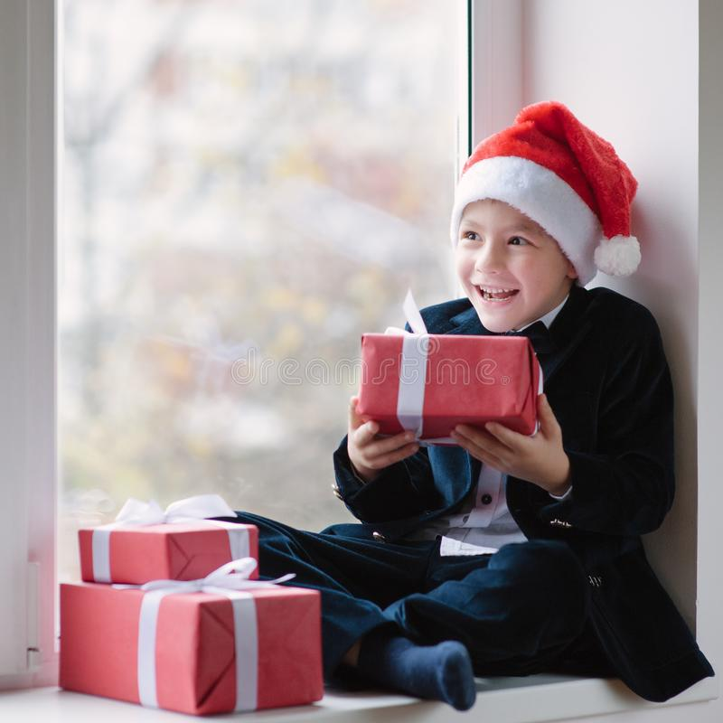 Happy little boy in a jacket sits at window and holding gift royalty free stock photography