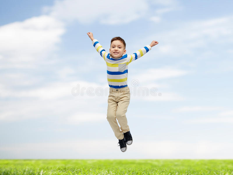 Happy little boy jumping over blue sky and grass stock image