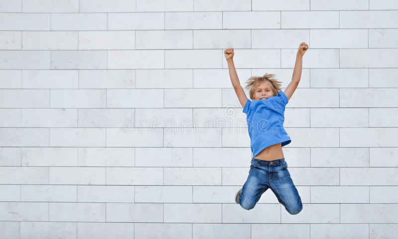 Happy little boy jumps on high. People, childhood, happiness, freedom, movement concept stock photo