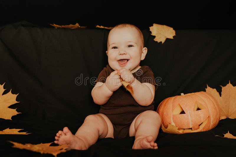 Happy little boy kid laughing with Halloween pumpkin Jack. On dark background with autumn leaves stock images