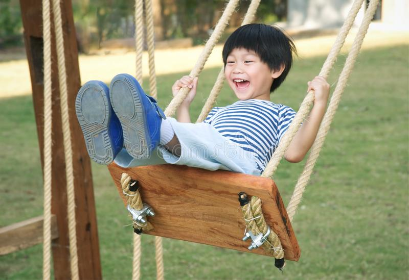 Happy little boy laughing and swinging on a swing royalty free stock images