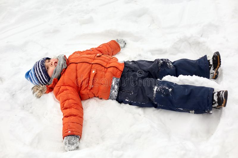 Happy little boy making snow angels in winter royalty free stock images