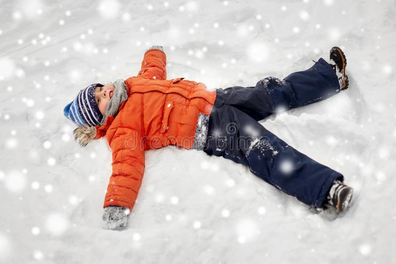 Happy little boy making snow angels in winter royalty free stock photo