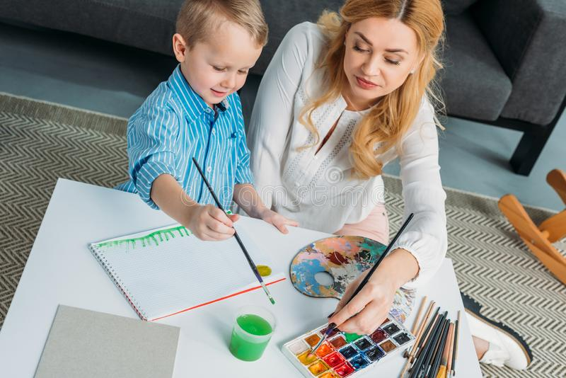Happy little boy and mother painting stock images